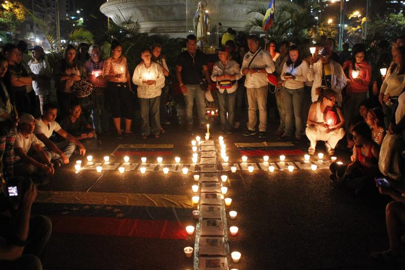 Anti-government protesters place candles next to photographs of victims of violence during a prayer ceremony in Caracas