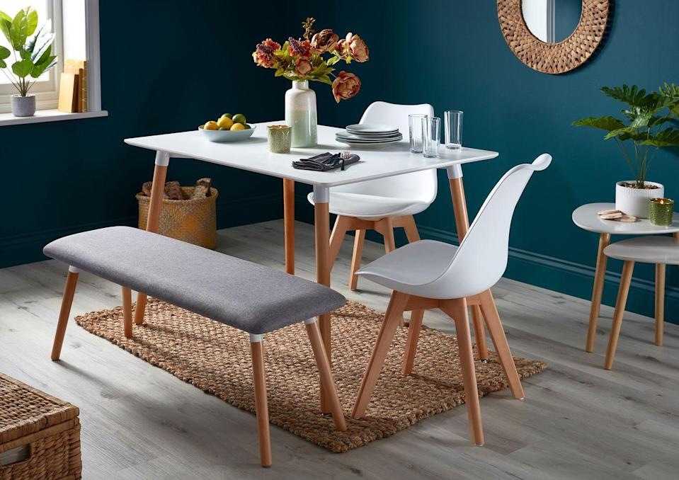 """<p>The <a href=""""https://www.homebase.co.uk/chloe-4-seater-dining-set-2-chairs-1-bench_p577311"""" rel=""""nofollow noopener"""" target=""""_blank"""" data-ylk=""""slk:Chloe 4-Seater Dining Set"""" class=""""link rapid-noclick-resp"""">Chloe 4-Seater Dining Set</a> (£215) offers a more flexible dining experience, while the rich, deep green walls (<a href=""""https://www.homebase.co.uk/elle-decoration-by-crown-flat-matt-paint-botanical-noir-2-5l_p558682"""" rel=""""nofollow noopener"""" target=""""_blank"""" data-ylk=""""slk:Botanical Noir by Elle Decoration"""" class=""""link rapid-noclick-resp"""">Botanical Noir by Elle Decoration</a>) works in harmony with the natural textures.<br></p>"""