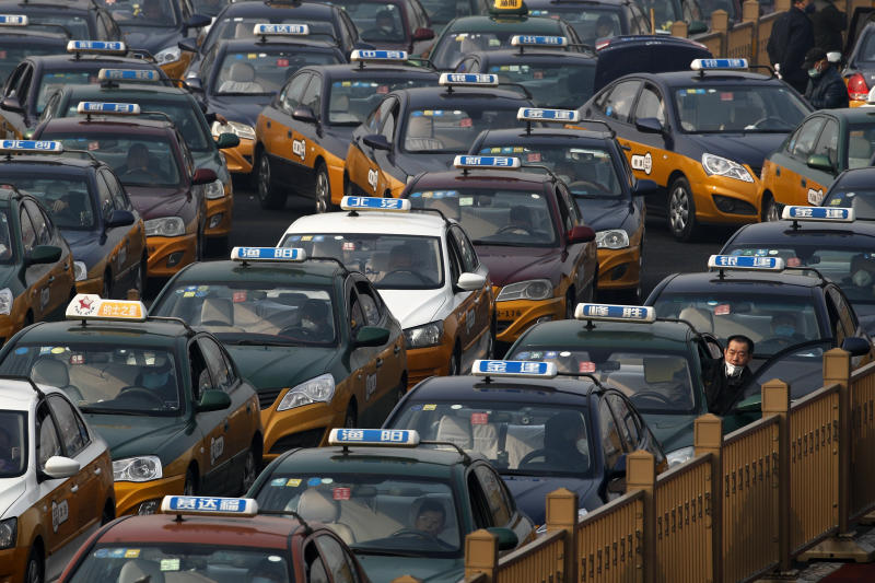A taxi driver looks out from his car as they pile up to wait for customers at the train station in Beijing, Tuesday, Feb. 11, 2020. China's daily death toll from a new virus topped 100 for the first time and pushed the total past 1,000 dead, authorities said Tuesday after leader Xi Jinping visited a health center to rally public morale amid little sign the contagion is abating. (AP Photo/Andy Wong)