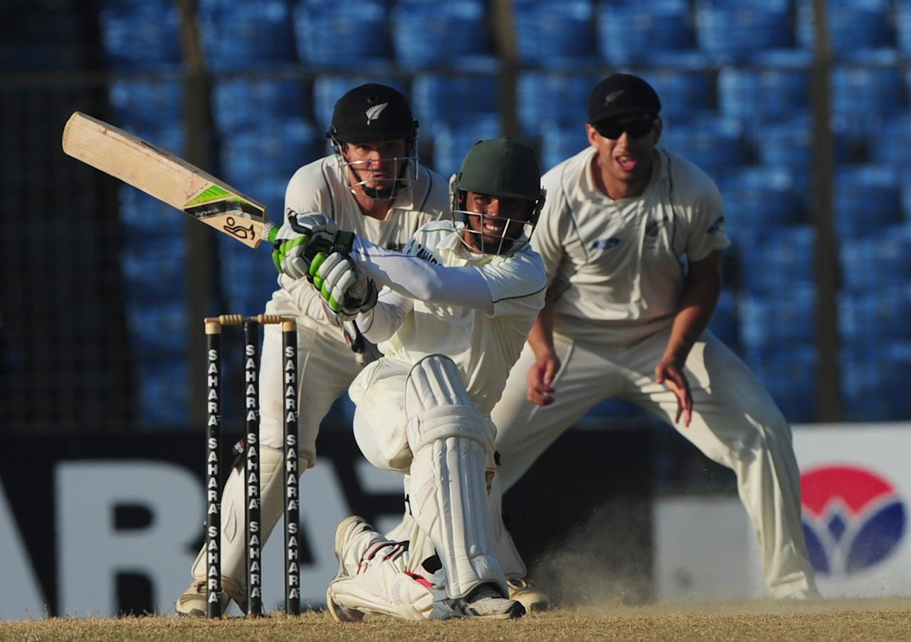 Bangladesh batsman Mominul Haque (C) plays a shot as New Zealand wicketkeeper B J Walting (L) and cricketer Ross Taylor (R) look on during the fifth and final day of the first cricket Test match between Bangladesh and New Zealand at The Zahur Ahmed Chowdhury Stadium in Chittagong on October 13, 2013. AFP PHOTO/Munir uz ZAMAN        (Photo credit should read MUNIR UZ ZAMAN/AFP/Getty Images)
