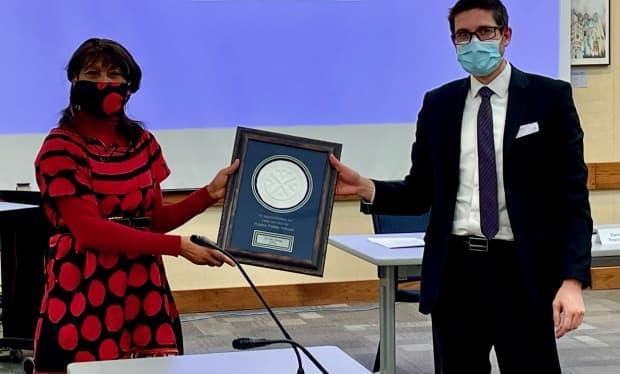 Dr. Jane Ekong receives a plaque of service from the Regina Public School Board.
