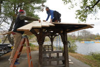 Contractor Jon Pope, left, works with Andrew Ullman as they repair the roof on a rustic shelter on the Peninsula beside Prospect Lake in Prospect Park, Sunday, Nov. 15, 2020, in the Brooklyn borough of New York. (AP Photo/Kathy Willens)