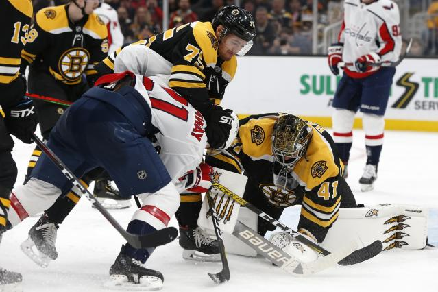 Boston Bruins' Jaroslav Halak (41) covers the puck as Connor Clifton (75) defends against Washington Capitals' Garnet Hathaway (21) during the second period of an NHL hockey game in Boston, Saturday, Nov. 16, 2019. (AP Photo/Michael Dwyer)