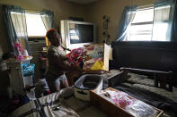 Patricia Mingo Lavergne salvages baby clothes she had been collecting for her unborn granddaughter, as she returns to her damaged home for the first time in Lake Charles, La., in the aftermath of Hurricane Laura, Sunday, Aug. 30, 2020. (AP Photo/Gerald Herbert)