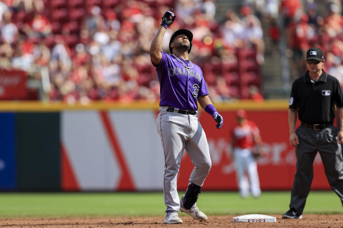 Colorado Rockies' Elias Diaz reacts after hitting an RBI-double during the second inning of a baseball game against the Cincinnati Reds in Cincinnati, Saturday, June 12, 2021. (AP Photo/Aaron Doster)