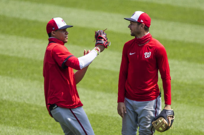 """FILE - Washington Nationals shortstop Trea Turner, right, watches teammate Juan Soto catch a fly ball during an intrasquad baseball game at Nationals Park in Washington, in this Sunday, Aug. 2, 2020, file photo. Juan Soto and Trea Turner are the key to the Washington Nationals lineup; both finished in the top seven in NL MVP voting last season. They also could be the key to the club's future, if they eventually sign the long-term deals the Nationals have tried to get done, so far unsuccessfully. """"What a duo,"""" manager Dave Martinez said Tuesday, Feb. 23, 2021, after Washington's first official full-squad workout of spring training in West Palm Beach, Florida. (AP Photo/Manuel Balce Ceneta, File)"""