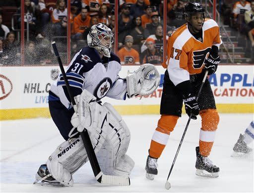 Winnipeg Jets goalie Ondrej Pavelec, left, and Philadelphia Flyers defenseman Wayne Simmonds watch the action in the second period of an NHL hockey game, Saturday, Feb 23, 2013, in Philadelphia. Simmonds scored the game winning goal in the Flyers' 5-3 win. (AP Photo/Tom Mihalek)