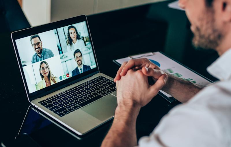 Businessman talking to his colleagues about business plan in video conference. Corporate business team using laptop for a online meeting in video call. Young man working at home. Shot of unrecognizable businessman using a laptop for web conference.