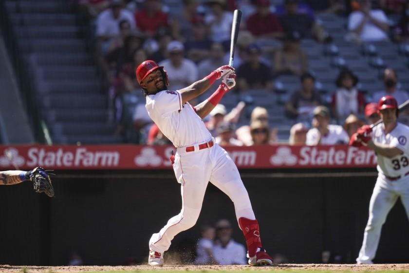 Los Angeles Angels' Jo Adell hits a home run during the sixth inning of a baseball game against the Texas Rangers Sunday, Sept. 5, 2021, in Anaheim, Calif. Jack Mayfield (9) also scored. (AP Photo/Ashley Landis)