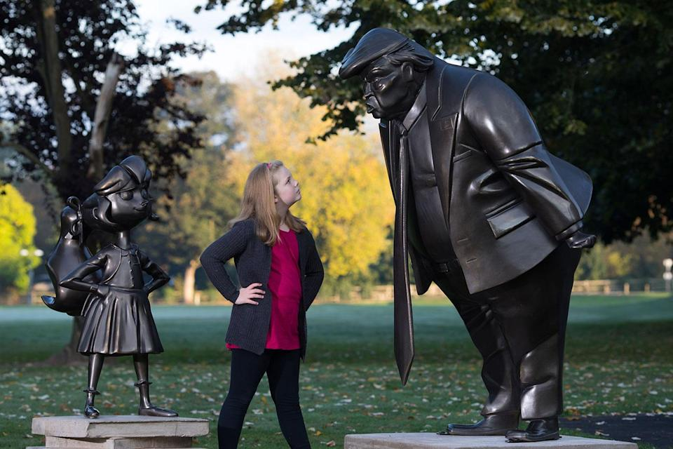 Mollie Sutton, eight, from Romford takes a look at a statue of Roald Dahl's Matilda which was unveiled in Great Missenden in Buckinghamshire, alongside one of President Donald Trump, to celebrate the 30th Anniversary of Matilda the novel. (David Parry/PA Wire/PA Images)