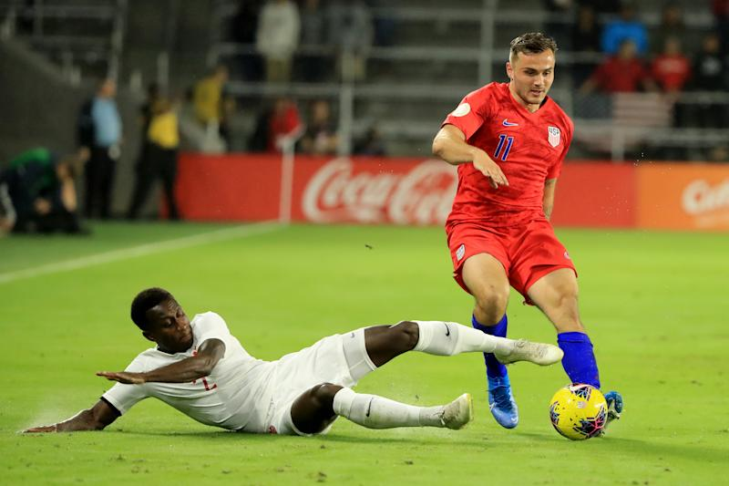 Jordan Morris (11) tries to avoid the tackle of Canada's Richie Laryea on Friday in Orlando. The USMNT won 4-1 in the CONCACAF Nations League. (Photo by Sam Greenwood/Getty Images)