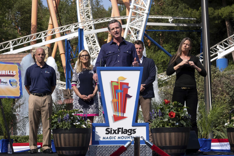 California Gov. Gavin Newsom welcomes the public to Six Flags Magic Mountain in Santa Clarita, Calif. on Wednesday, June 16, 2021. In the background, from left, are; Michael Spanos, President of Six Flags, LA county supervisor Kathryn Barger and state senator Henry Stern. Newsom continued his tour of the state after lifting most COVID-19 restrictions Tuesday. (David Crane/The Orange County Register via AP)