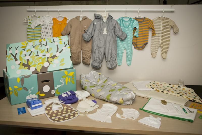 This photo taken on Aug. 15, 2012 shows the contents of the Finnish baby box, in Helsinki, Finland. Finland's social security service has given a baby box to Prince William and former Catherine Middleton, who are expecting their first baby in mid-July. The brightly colored cardboard box doubles as a cot, complete with mattress and sheets, and contains numerous baby items including a sleeping bag, jump suits, socks, pants, hats, bonnets and diapers. Maternity packages have been given to expectant mothers in Finland since 1938. (AP Photo/Lehtikuva, Roni Rekomaa) FINLAND OUT