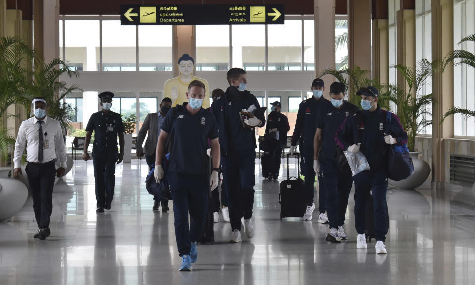 England cricketers walk along the arrivals terminal at Mattala Rajapaksa International airport in Hambantota, Sri Lanka, Sunday, Jan. 3, 2021. Team allrounder Moeen Ali was isolating in Sri Lanka on Monday after testing positive for the coronavirus upon his arrival in the South Asian country for the team's two-test cricket tour. Pace bowler Chris Woakes has been deemed as a possible close contact of Ali and was also observing a period of self-isolation in developments which have cast an early shadow on the tour that takes place weeks after a white-ball trip to South Africa was derailed by a spate of positive COVID-19 results. (AP Photo/Nuwan Jayasekara)