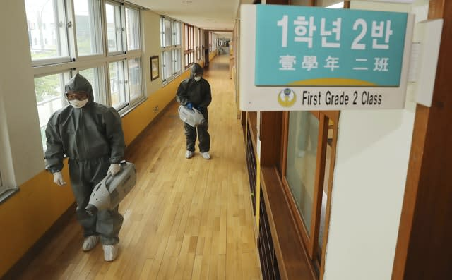 Workers disinfect as a precaution against the new coronavirus ahead of school reopening at an elementary school in Gwangju, South Korea