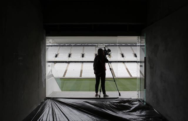 A journalist records a piece-to-camera at the construction site of the Arena de Sao Paulo Stadium, which will host the opening soccer match of the 2014 FIFA World Cup, in Sao Paulo April 15, 2014. Corinthians have taken formal control of the stadium that will host the opening match of this year's World Cup but officials said on Tuesday there is still a lot of work to do before the arena is ready to host big games. REUTERS/Nacho Doce (BRAZIL - Tags: SPORT SOCCER WORLD CUP BUSINESS CONSTRUCTION MEDIA)