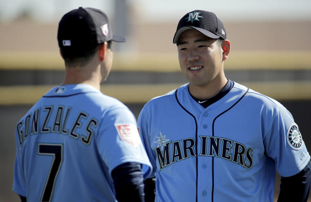 Seattle Mariners pitcher Yusei Kikuchi, from Japan, talks to pitcher Marco Gonzales during spring training baseball practice Tuesday, Feb. 12, 2019, in Peoria, Ariz. (AP Photo/Charlie Riedel)