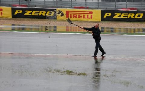 A worker unclogs a drain during a delay in the second practice session for the Formula One U.S. Grand Prix auto race at the Circuit of the Americas, Friday, Oct. 23, 2015, in Austin, Texas. The second practice session was called off by officials due to the weather - Credit: ap