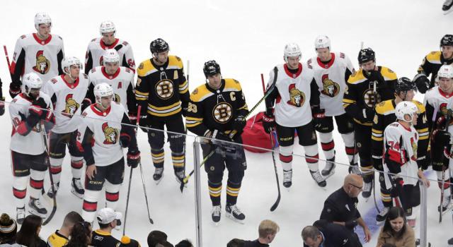 Members of the Ottawa Senators and Boston Bruins watch as medical workers attend to Senators forward Scott Sabourin, who was injured following a collision with Bruins' forward David Backes on Saturday night. (AP Photo/Charles Krupa)