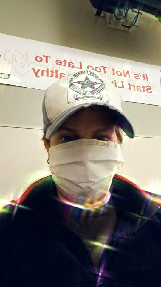 woman wearing a face mask and a baseball cap in the waiting room of the ER