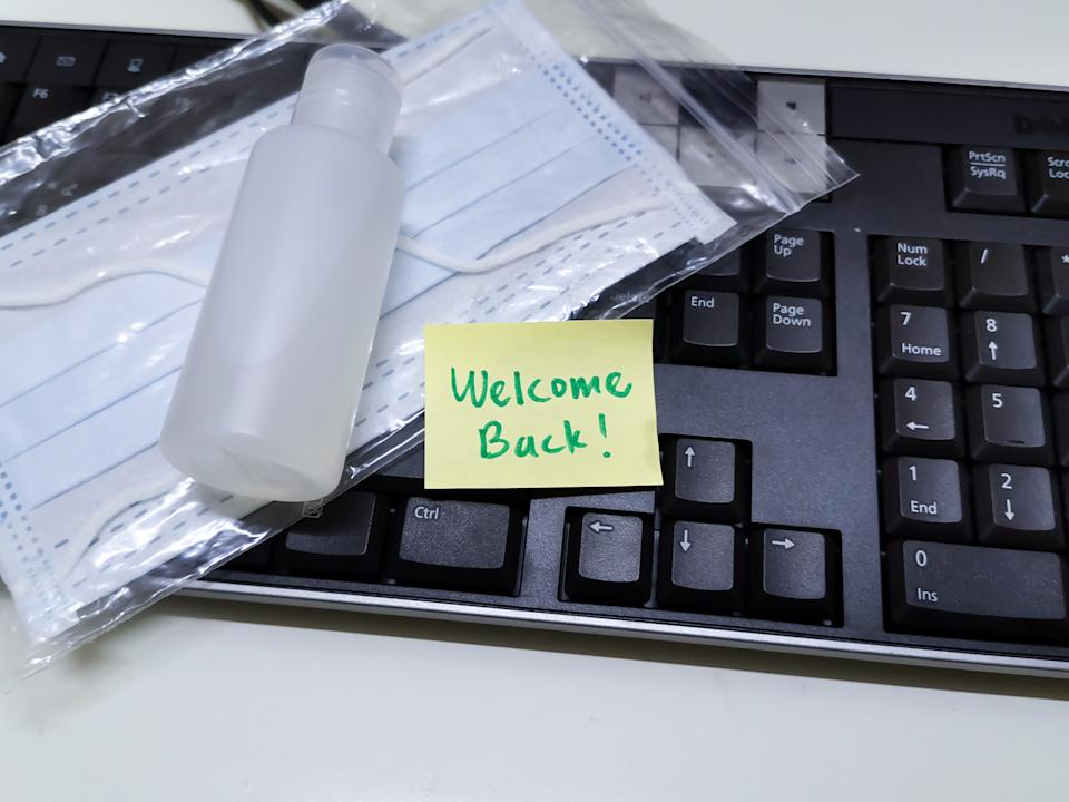 Welcome note with hand sanitizer and mask on work keyboard; Back to work note with alcohol gel to prevent coronavirus / infection