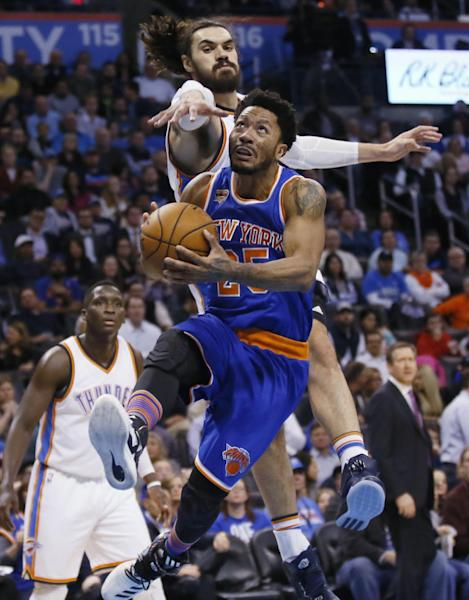 New York Knicks guard Derrick Rose drives to the basket in front of Oklahoma City Thunder center Steven Adams, top, during the second quarter of an NBA basketball game in Oklahoma City, Wednesday, Feb. 15, 2017. (AP Photo/Sue Ogrocki)