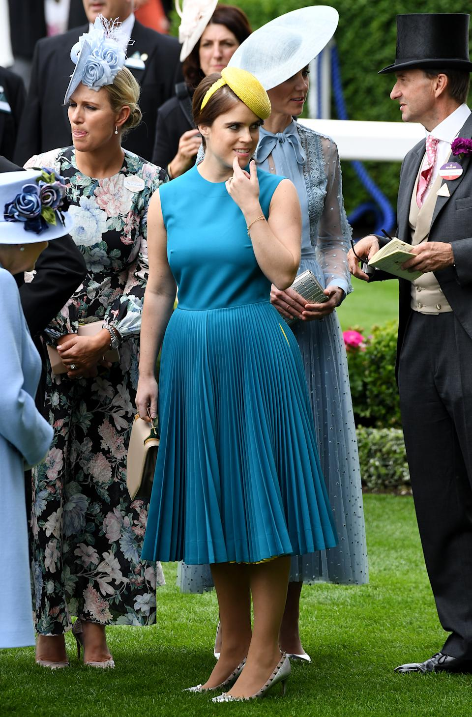 """Princess Eugenie wore a teal sleeveless number with yellow stripe detailing by <a href=""""https://fave.co/2wZvU6z"""" rel=""""nofollow noopener"""" target=""""_blank"""" data-ylk=""""slk:Calvin Klein"""" class=""""link rapid-noclick-resp"""">Calvin Klein</a> with a bold yellow beret-style hat. <em>[Photo: PA]</em>"""