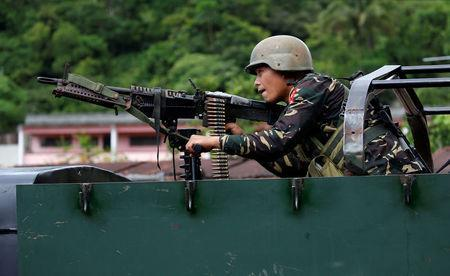 A government soldier holds a weapon aboard an armoured fighting vehicle (AFV) as soldiers advance their position in Marawi City, Philippines May 28, 2017. REUTERS/Erik De Castro