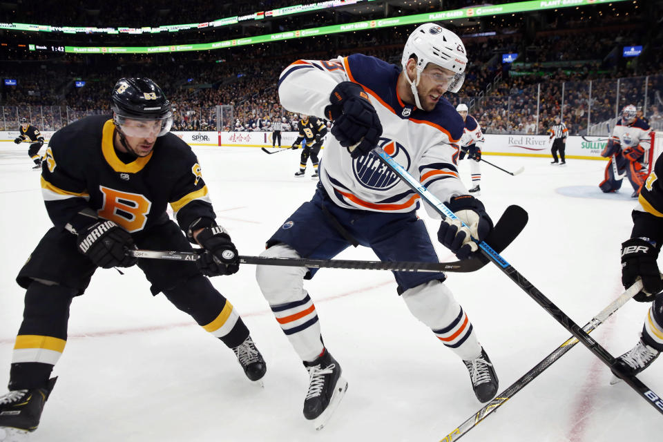Edmonton Oilers' Riley Sheahan (23) defends against Boston Bruins' Brad Marchand (63) during the first period on an NHL hockey game in Boston, Saturday, Jan. 4, 2020. (AP Photo/Michael Dwyer)
