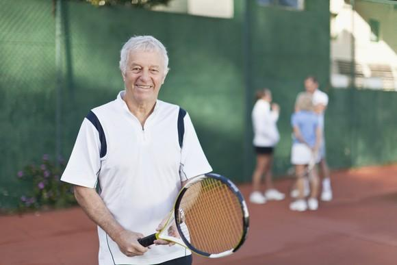Senior man in tennis outfit holding racket.