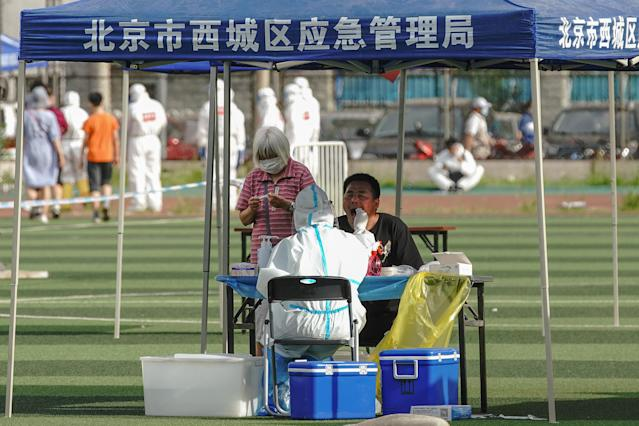 A Chinese nurse wearing a protective suit takes a nucleic acid test from a man at Guangan Sport Center for citizens who visited or live near the Xinfadi Market on Thursday. (Getty)