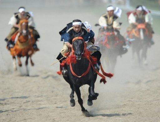 """People in samurai costumes ride horses during a horse racing event at the annual """"Soma Nomaoi"""" festival in Minamisoma, Fukushima Prefecture, on July 28. The traditional festival kicked off for the first time since the 2011 quake-tsunami disaster"""