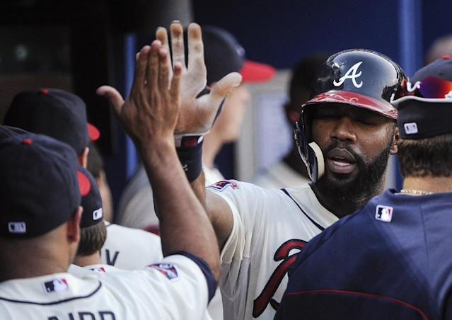 Atlanta Braves' Jason Heyward is congratulated in the dugout after scoring against the San Diego Padres on a single by Chris Johnson during the fourth inning of a baseball game, Saturday, July 26, 2014, in Atlanta. (AP Photo/John Amis)
