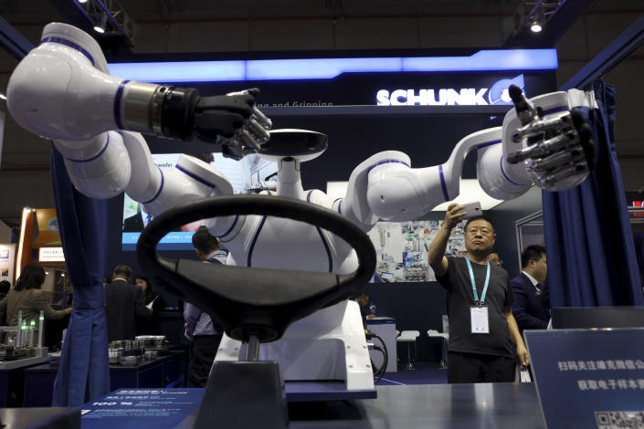 In this Wednesday, Nov. 6, 2019, file photo, a visitor takes a photo of a robot that can be used to operate a vehicle during the China International Import Expo in Shanghai. The sprawling import fair into its second year is meant to demonstrate China's willingness to open its domestic markets.(AP Photo/Ng Han Guan, File)