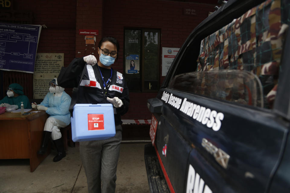 """Punam Karmacharya, 22, of the RNA-16 volunteer group, carries a box containing swab samples of patients to deliver it to a testing center, at a hospital in Bhaktapur, Nepal, Tuesday, May 26, 2020. RNA-16 stands for """"Rescue and Awareness"""" and the 16 kinds of disasters they have prepared to deal with, from Nepal's devastating 2015 earthquake to road accidents. But the unique services of this group of three men and a woman in signature blue vests in the epidemic amount to a much greater sacrifice, said doctors, hospital officials and civic leaders. (AP Photo/Niranjan Shrestha)"""