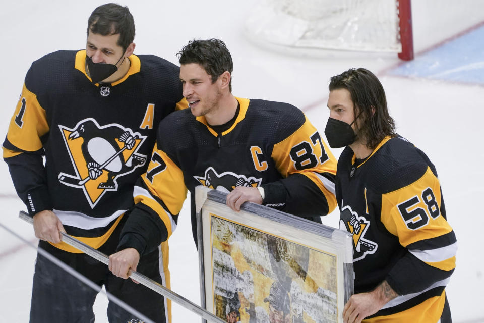 Pittsburgh Penguins' Sidney Crosby, center, poses with Evgeni Malkin, left, and Kris Letang during a ceremony honoring his 1000th NHL hockey game with the team before an NHL hockey game against the New York Islanders, Saturday, Feb. 20, 2021, in Pittsburgh. (AP Photo/Keith Srakocic)