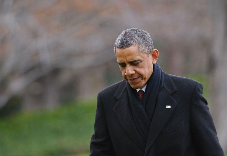 """US President Barack Obama walks across the South Lawn upon return to the White House on December 27, 2012 in Washington. Obama will host top congressional leaders including his bitter Republican rivals on Friday in a last-ditch bid to halt America's slide over the so-called """"fiscal cliff."""""""
