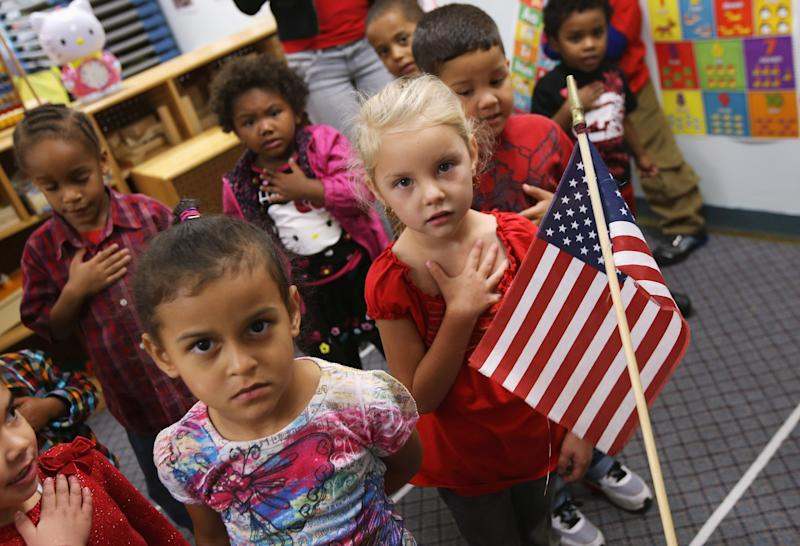 WOODBOURNE, NY - SEPTEMBER 20:  Children recite the Pledge of Allegiance at the beginning of the school day at the federally-funded Head Start school on September 20, 2012 in Woodbourne, New York. The school provides early education, nutrition and health services to 311 children from birth through age 5 from low-income families in Sullivan County, one of the poorest counties in the state of New York. The county Head Start Program was expanded with a $1 million grant from President Obama's 2009 stimulus bill, the American Recovery and Reinvestment Act. Head Start, administered by the U.S. Department of Health and Human Services, is the longest-running early education program for children of low-income families in the United States.  (Photo by John Moore/Getty Images)
