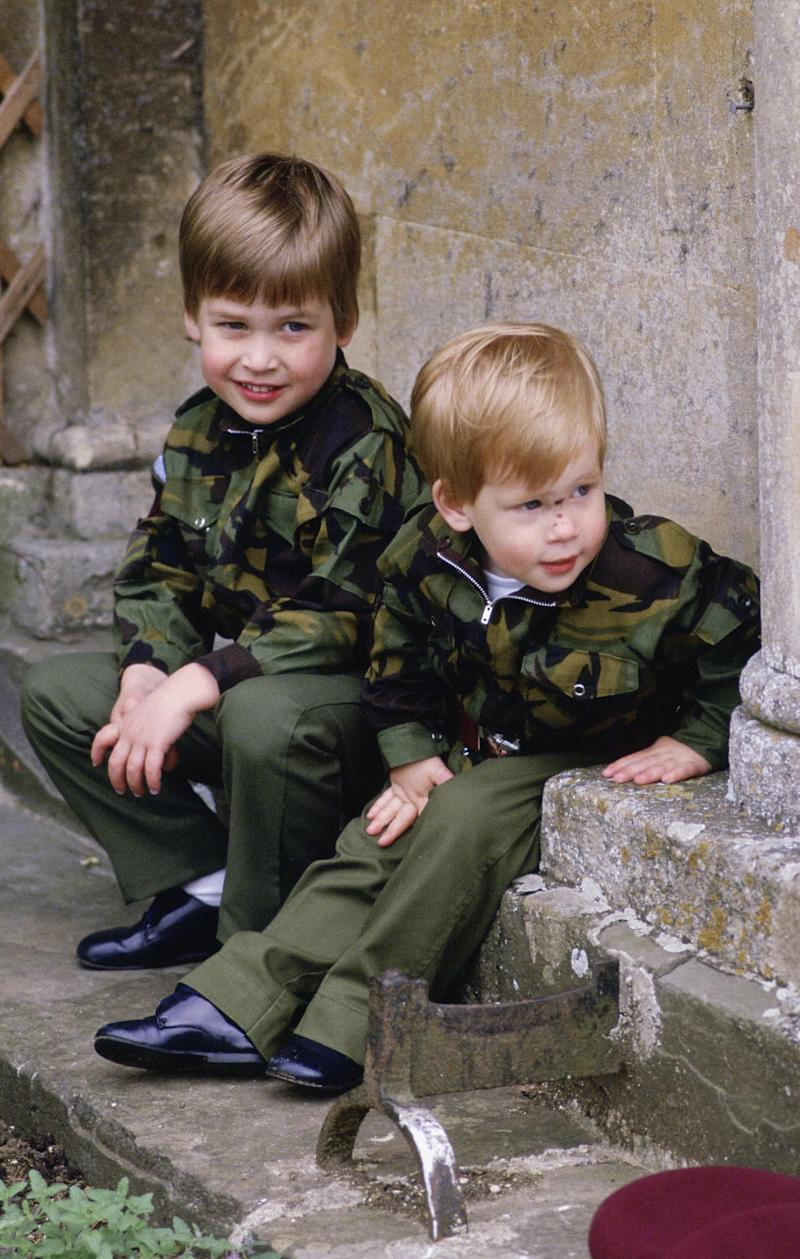 Prince Harry and Prince William sit together on the steps of Highgrove House wearing army uniforms on July 18, 1986 in Tetbury, England.