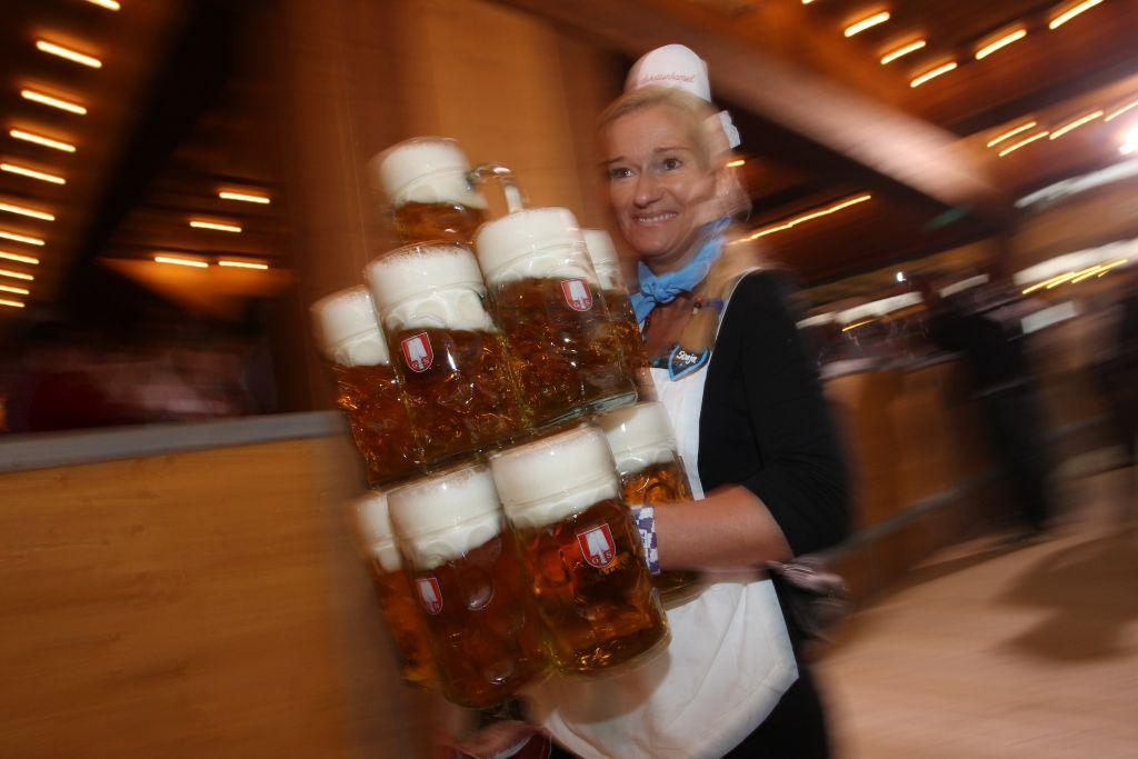 A waitress carries eleven beer mugs at a beer tent.