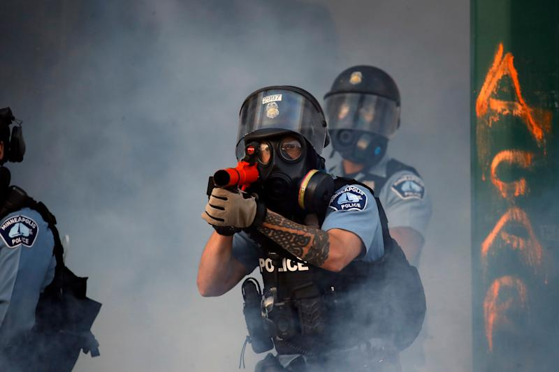 """A police officer prepares to shoot tear gas on on May 29, 2020. in Minneapolis. <a href=""""https://www.huffingtonpost.ca/entry/us-protests-curfews-george-floyd_ca_5ed38f95c5b6eefb02357739?hqq"""" target=""""_blank"""" rel=""""noopener noreferrer"""">Protests continued</a> following the death of George Floyd who died after being restrained by Minneapolis police officers on Memorial Day."""