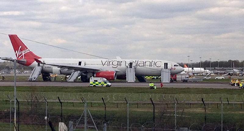 Virgin Atlantic Airbus A330 bound for Orlando sits on the runway at Gatwick Airport, England after it made an a full emergency landing. Virgin Atlantic said four people suffered minor injuries after a plane bound from Britain to Florida made an emergency landing at London's Gatwick Airport on Monday. The airline said that all passengers and crew have safely disembarked the plane, but declined to provide further details on the nature of the injuries, who was affected or what caused the emergency landing.(AP Photo/Lorna Willson/PA) UNITED KINGDOM OUT