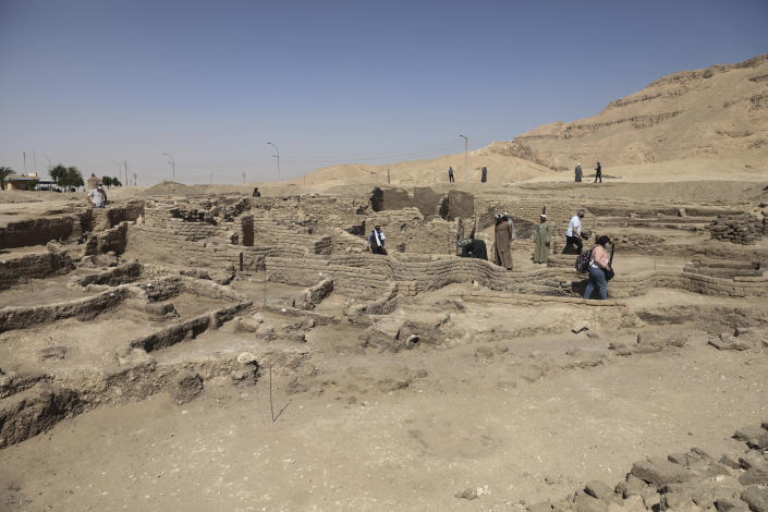 People stand in a 3,000-year-old lost city in Luxor province, Egypt, Saturday, April 10, 2021. The newly unearthed city is located between the temple of King Rameses III and the colossi of Amenhotep III on the west bank of the Nile in Luxor. The city continued to be used by Amenhotep III's grandson Tutankhamun, and then his successor King Ay. (AP Photo/Mohamed Elshahed)