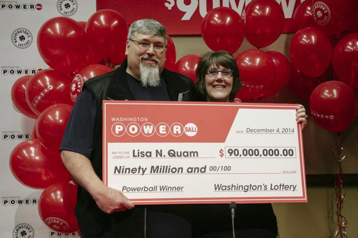 Lisa Quam and her husband Everett hold a check for $90 million during a news conference in Olympia, Washington December 4, 2014 in this handout picture provided by the Washington State lottery. Lisa Quam on Thursday claimed a $90 million Powerball lottery jackpot after buying a ticket for the first time, and said she would quit her job at plane maker Boeing Co and buy a new Subaru. REUTERS/Washington State Lottery/Handout (UNITED STATES - Tags: SOCIETY TPX IMAGES OF THE DAY) ATTENTION EDITORS - THIS PICTURE WAS PROVIDED BY A THIRD PARTY. REUTERS IS UNABLE TO INDEPENDENTLY VERIFY THE AUTHENTICITY, CONTENT, LOCATION OR DATE OF THIS IMAGE. FOR EDITORIAL USE ONLY. NOT FOR SALE FOR MARKETING OR ADVERTISING CAMPAIGNS. NO SALES. NO ARCHIVES. THIS PICTURE IS DISTRIBUTED EXACTLY AS RECEIVED BY REUTERS, AS A SERVICE TO CLIENTS