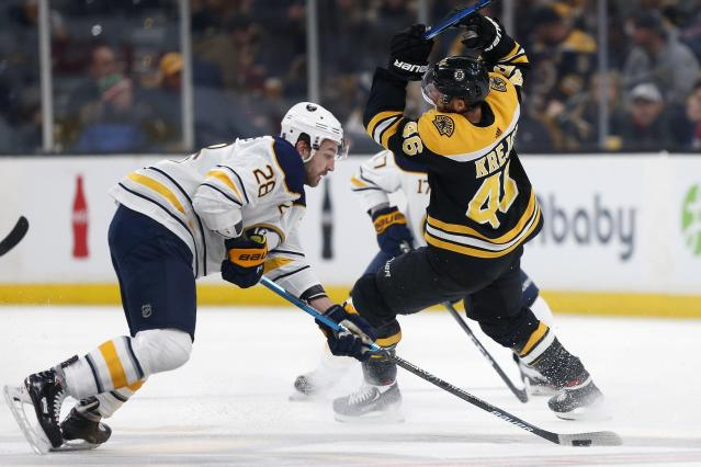 Buffalo Sabres' Zemgus Girgensons (28) gains control of the puck from Boston Bruins' David Krejci (46) during the first period of an NHL hockey game in Boston, Sunday, Dec. 16, 2018. (AP Photo/Michael Dwyer)