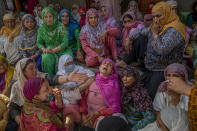 Women gather around the wailing mother, center in pink, of policeman Waseem Ahmed, who was killed in a shootout, on the outskirts of Srinagar Indian controlled Kashmir, Sunday, June 13, 2021. Two civilians and two police officials were killed in an armed clash in Indian-controlled Kashmir on Saturday, police said, triggering anti-India protests who accused the police of targeting the civilians. (AP Photo/ Dar Yasin)