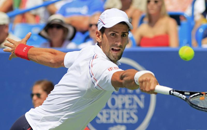 Novak Djokovic, from Serbia, returns a serve against Juan Martin del Potro, from Argentina, during a semifinal match at the Western & Southern Open tennis tournament, Saturday, Aug. 18, 2012, in Mason, Ohio. (AP Photo/Al Behrman)