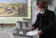 An elderly woman casts her ballot during the presidential elections in Gornaya Maevka village, about 25 kilometers (16 miles) south-west of Bishkek, Kyrgyzstan, Sunday, Jan. 10, 2021. Voters in Kyrgyzstan are casting ballots in an election that will also determine how much power the next president has. The Sunday vote follows the ouster of the nation's previous president in October. (AP Photo/Vladimir Voronin)