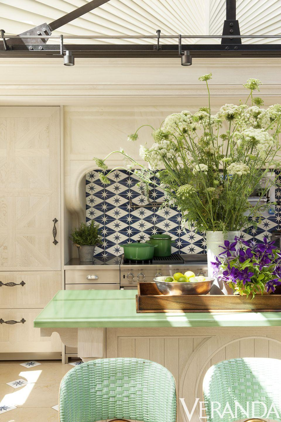 """<p>This Los Angeles kitchen features a tile backsplash with a diamond and star pattern (<a href=""""http://www.solarantiquetiles.com/"""" rel=""""nofollow noopener"""" target=""""_blank"""" data-ylk=""""slk:Solar Antique Tiles"""" class=""""link rapid-noclick-resp"""">Solar Antique Tiles</a>) in an inky blue and crips white palette that complements the wood grain cabinetry and mind green island top and chairs.</p>"""