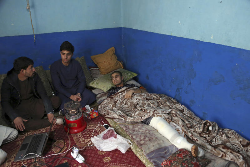 Nawid, a 21-year-old student who lost his brother and who was himself wounded in a deadly Taliban suicide attack on the Afghan capital's Green Village neighborhood earlier this month, receives visitor as he lies in bed at home in Kabul, Afghanistan, Tuesday, Jan. 29, 2019. Kabul residents are wary of peace talks with the Taliban, even as Afghan officials express hope that negotiations could lead to lasting peace in their war-ravaged country. (AP Photo/Rahmat Gul)
